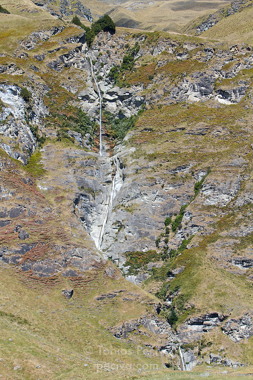 Series of waterfalls cascading down a cliff near the Treble Cone ski field, outside Wanaka, New Zealand.