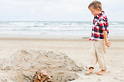 4 year-old ,Beckem Danger Edwards inspects a beach fire pit on Mustang Island at the seaside village/community of Cinnamon Shore in Port Aransas, Texas.