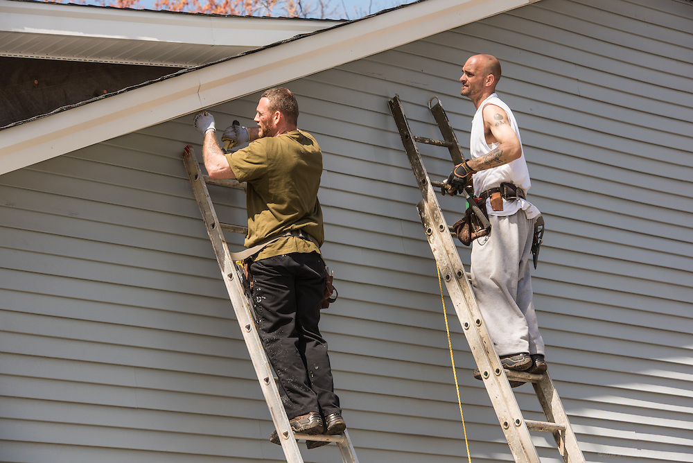 Community members and New Legacy residents Kenny Tilley, 34, and George Coy, 40, work at a project Level of Excellence is doing in partnership with The Fuller Center for Housing near Shawnee Park. (Photo by Brian Bohannon)