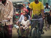 05 NOVEMBER 2014 - SITTWE, RAKHINE, MYANMAR:  A Rohingya Muslim woman and her son in a rickshaw taxi on the main road into a Rohingya IDP camp near Sittwe. After sectarian violence devastated Rohingya communities and left hundreds of Rohingya dead in 2012, the government of Myanmar forced more than 140,000 Rohingya Muslims who used to live in and around Sittwe, Myanmar, into squalid Internal Displaced Persons camps. The government says the Rohingya are not Burmese citizens, that they are illegal immigrants from Bangladesh. The Bangladesh government says the Rohingya are Burmese and the Rohingya insist that they have lived in Burma for generations. The camps are about 20 minutes from Sittwe but the Rohingya who live in the camps are not allowed to leave without government permission. They are not allowed to work outside the camps, they are not allowed to go to Sittwe to use the hospital, go to school or do business. The camps have no electricity. Water is delivered through community wells. There are small schools funded by NOGs in the camps and a few private clinics but medical care is costly and not reliable.  PHOTO BY JACK KURTZ