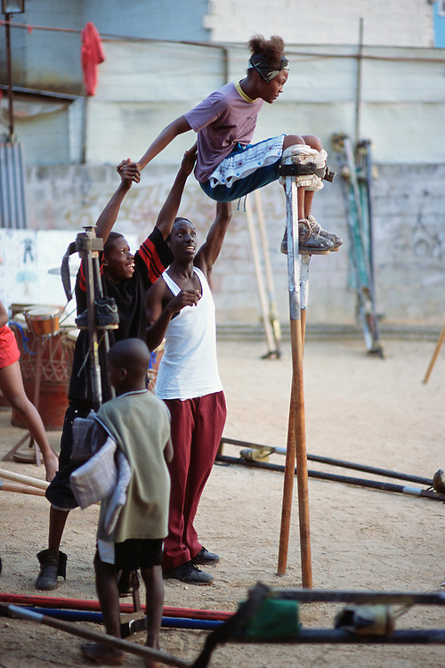 "Trinidad and Tobago ""MOKO JUMBIES: The Dancing Spirits of Trinidad"".(Melissa Brown is raised onto her stilts by Chester Bacchus and Roland Williams.).A photo essay about a stilt walking school in Cocorite, Trinidad..Dragon Glen de Souza founded the Keylemanjahro School of Art & Culture in 1986. The main purpose of the school is to keep children off the streets and away from drugs..He first taught dances like the Calypso, African dance and the jig with his former partner Cathy Ann Samuel.  Searching for other activities to engage the children in, he rediscovered the art of stilt-walking, a tradition known in West Africa as the Moko Jumbies , protectors of the villages and participants in religious ceremonies. The art was brought to Trinidad by the slave trade and soon forgotten..Today Dragon's school has over 100 members from age 4 and up..His 2 year old son Mutawakkil is probably the youngest Moko Jumbie ever. The stilts are made by Dragon and his students and can be as high as 12-15 feet. The children show their artistic talents mostly at the annual Carnival, which today is unthinkable without the presence of the Moko Jumbies. A band can have up to 80 children on stilts and they have won many of the prestigious prizes and trophies that are awarded by the National Carnival Commission. Designers like  Peter Minshall , Brian Mac Farlane and Laura Anderson Barbata create dazzling costumes for the school which are admired by thousands of  spectators. Besides stilt-walking the children learn the limbo dance, drumming, fire blowing and how to ride  unicycles..The school is situated in Cocorite, a suburb of Port of Spain, the capital of Trinidad and Tobago..all images © Stefan Falke"