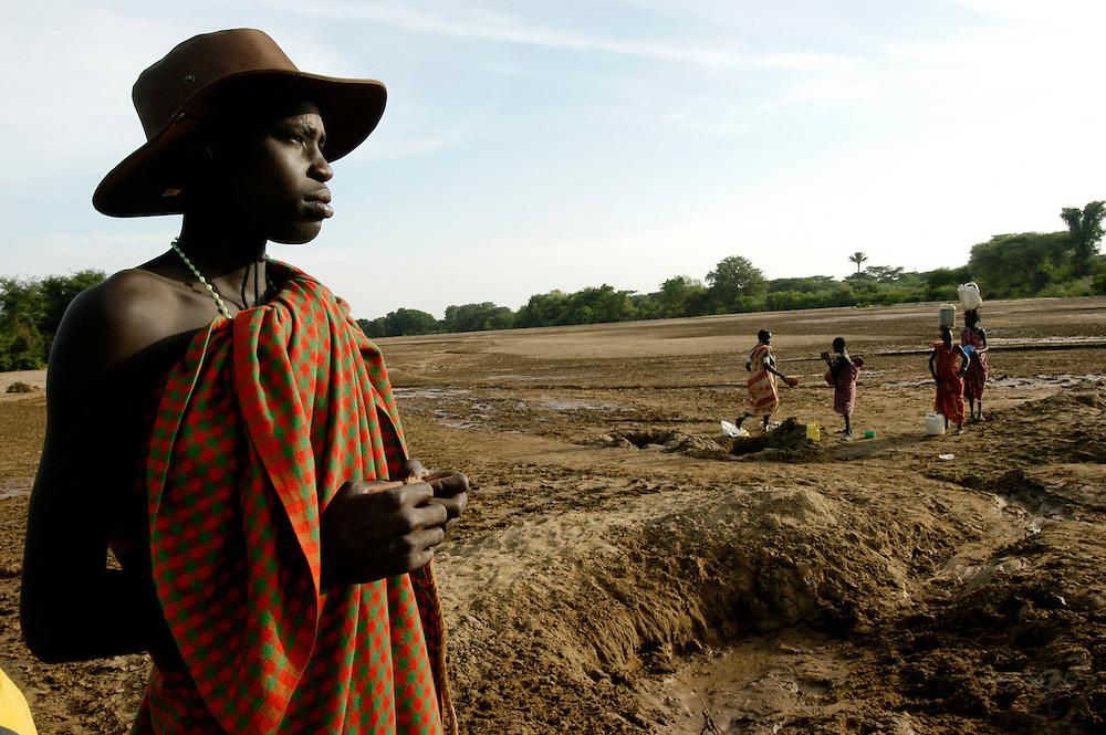 Toposa tribe men and woman draw water from a hole dug in the dry bed of the Singaita River in Eastern Equatoria province. Failed rainy seasons have severely affected several East African countries. Kapoeta, South Sudan. 27/09/2009
