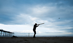 © Licensed to London News Pictures. 07/04/2014<br /> <br /> Saltburn, United Kingdom<br /> <br /> Michael Yates, 13, from Norwich plays cricket on the beach with his family as dark storm clouds form over Saltburn by the Sea in Cleveland.<br /> <br /> Photo credit : Ian Forsyth/LNP
