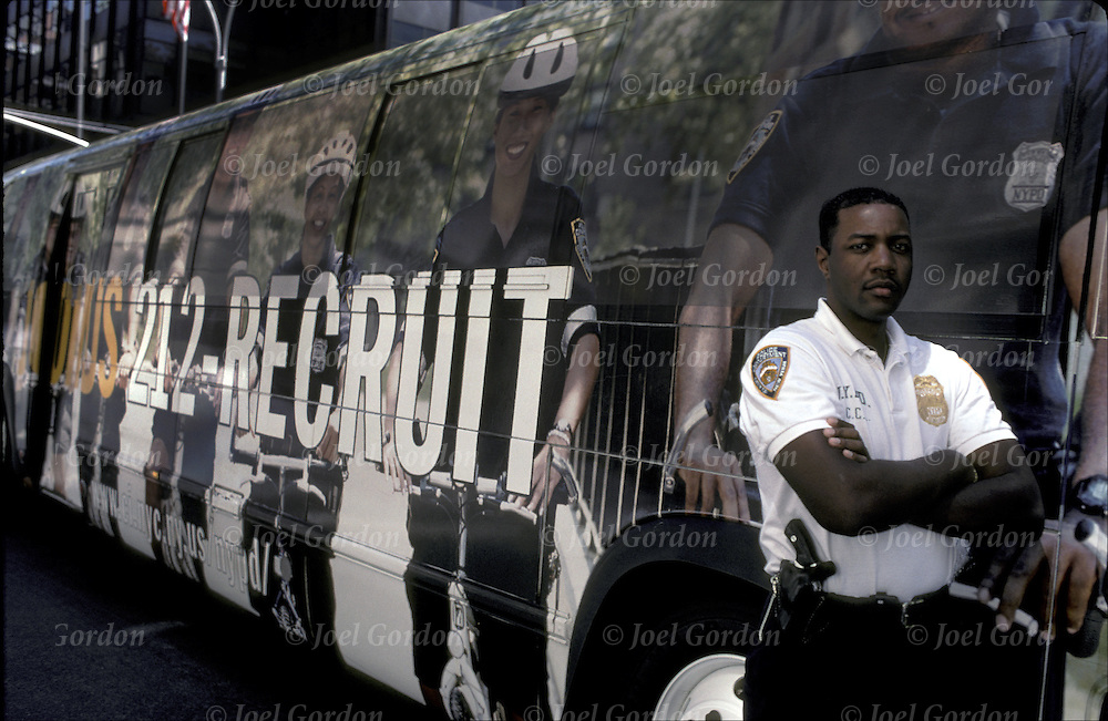 Officer standing next to ?212-RECRUIT? bus.- NYPD - city wide recruiting program - NYC