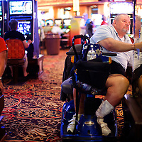 Men gamble on slot machines in Trump Plaza Casino in Atlantic City, NJ on September 3, 2014.  Economically the city is struggling, 4 casinos have already or will be closing in the near future, including Trump Plaza which shutters their doors on September 16.