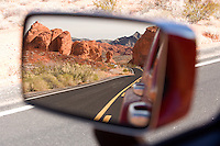 Rear view mirror displays the fiery red rock formations of Valley of Fire State Park in Nevada.
