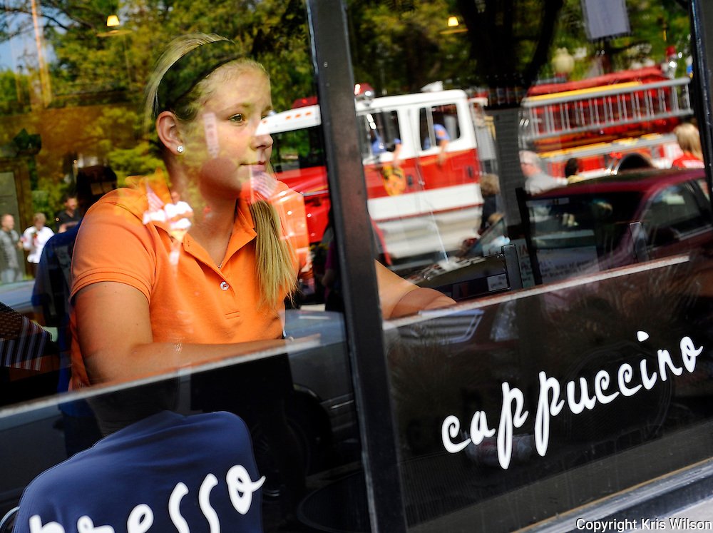Olivia Johanns glances out as the Jefferson City Patriot's Day parade passes by on High Street while finishing her shift at Cafe Via Roma.