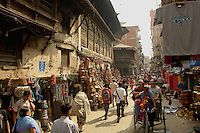 Busy street scene in Kathmandu's old town with vendors and travellers in a rickshaw.