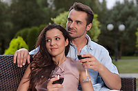 Beautiful young couple having red wine in park
