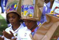 Stock photo of two African American girls wearing decorated paper bags as hats during the International Festival Kids' Day 2002