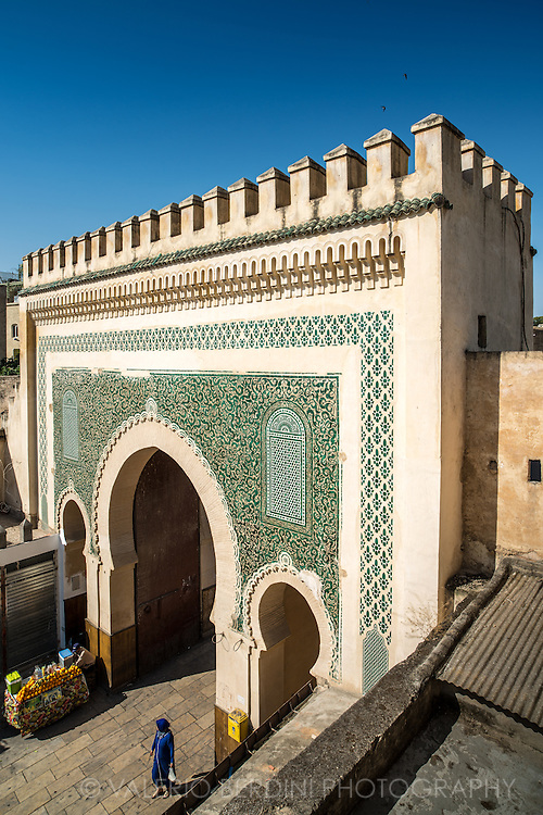 A woman walks through Bab Boujloud, a monumental gate that marks the entrance of one of the busiest areas of Fez medina. The gate (Bab) has blue ceramic tiles on the external facade and green in the internal.