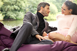 Couple Sitting on Large Cushion in Park