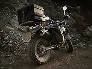 A motorbike loaded with storm cases is parked along a muddy track. Cao Bang province, Vietnam, Asia.