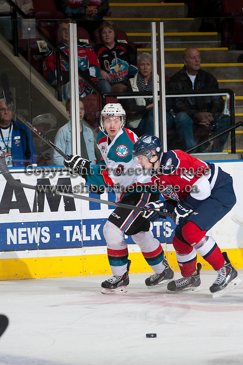 KELOWNA, CANADA - MARCH 23: Colten Martin #8 of the Kelowna Rockets makes a pass while being checked by Beau McCue #16 of the Tri-City Americans on March 23, 2014 at Prospera Place in Kelowna, British Columbia, Canada.   (Photo by Marissa Baecker/Shoot the Breeze)  *** Local Caption *** Colten Martin; Beau McCue;