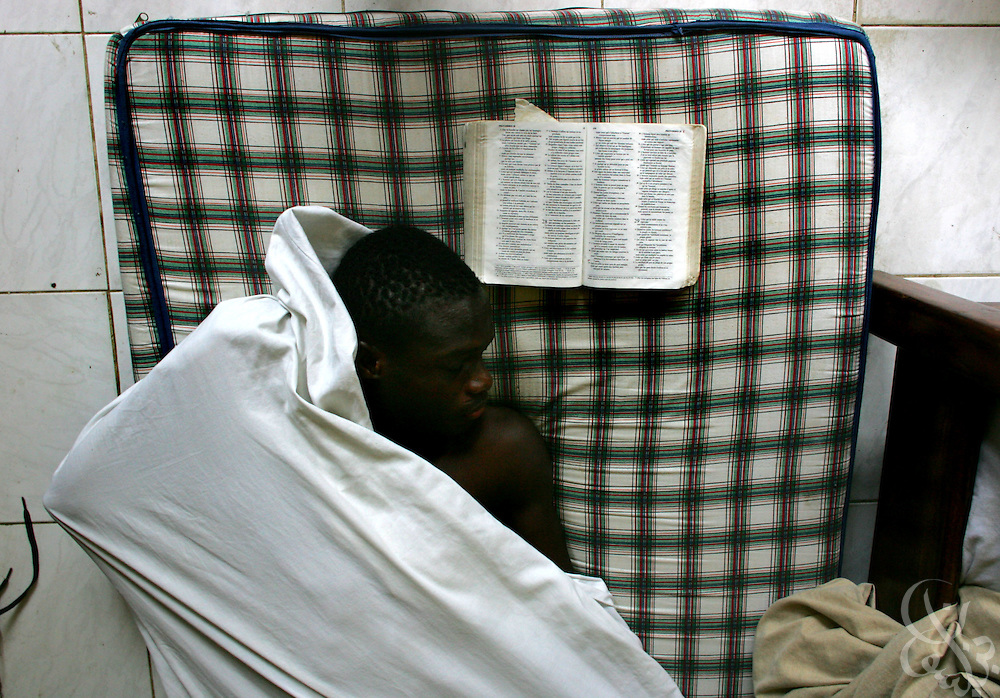 A teenage Ivorian football player naps next to his open bible following a morning training session at the ASEC football academy February 16, 2006 in Abidjan, Côte d'Ivoire. ASEC academy has an established history of producing top notch footballers who go on to play in the top European football leagues. Students live full time at the academy during the week but are allowed to return home on weekends.