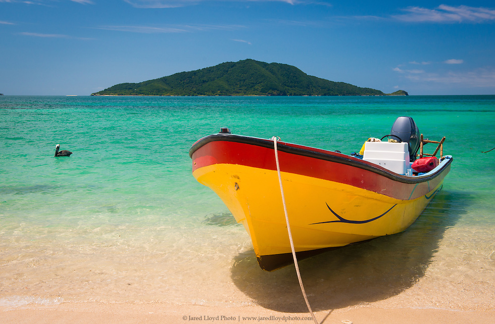 a brightly colored Mexican skiff sits beached at the edge of the Caribbean along Cayos Cochinos in Honduras