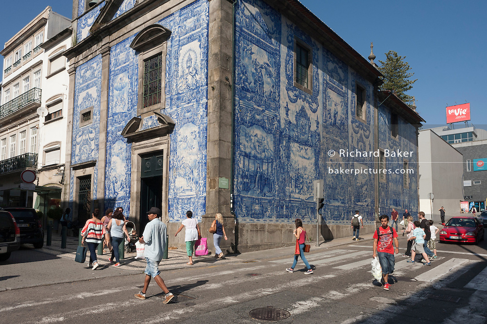 Pedestrians pass beneath traditional Azulejo tiles on the wall of Capela Das Almas (church), on Rua Santa Catarina Porto, Portugal. The panels depict scenes from the lives of various saints including the death of St Francis and the martyrdom of St Catherine. Eduardo Leite painted the tiles in a classic 18th-century style, though they actually date back only to the early 20th century.