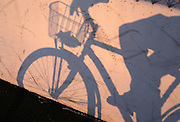 tinted replica of distorted shadow of person riding bicycle