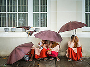 20 OCTOBER 2015 - YANGON, MYANMAR:   Buddhist nuns, also called Bhikkhuni, wait out a rain storm in Yangon, Myanmar. PHOTO BY JACK KURTZ