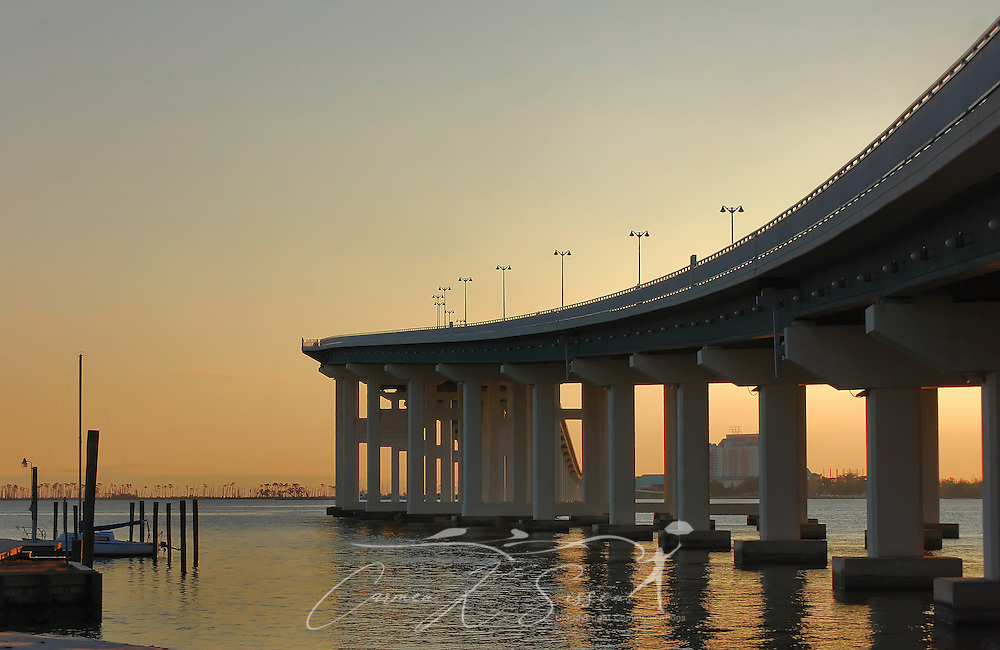 The sun sets on the Biloxi Bay Bridge, viewed from Front Beach in Ocean Springs, Mississippi, on Dec. 18, 2010. The bridge, part of U.S. Highway 90, connects the cities of Ocean Springs and Biloxi. The original bridge was destroyed by Hurricane Katrina in August 2005. The new bridge spans six lanes and includes a pedestrian walkway. (Photo by Carmen K. Sisson/Cloudybright)