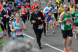 © Licensed to London News Pictures. 24/04/2016. London, UK. Spectators watch fancy dress and mass runners including a man dressed as a policeman run along The Highway towards Shadwell at the 2016 London Marathon.  Photo credit : Vickie Flores/LNP