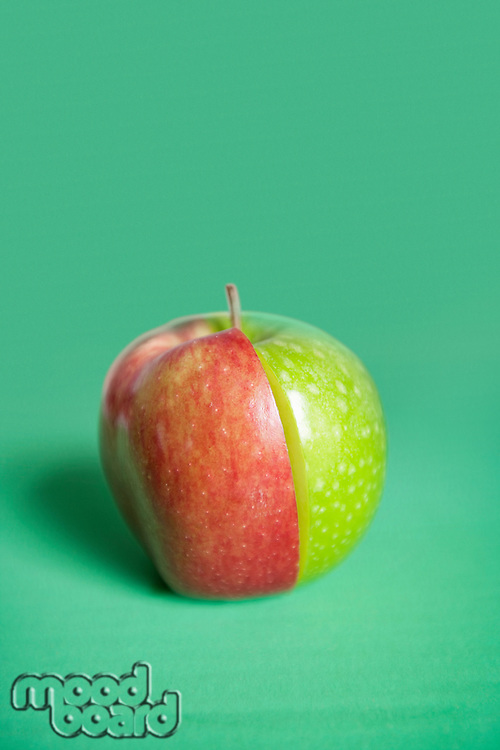 Red and green apple slices joined together over colored background
