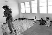 TEN, 5 Jahre, auf dem arm ihres Vaters der selber Aidskrank ist.  Die Kinder aus Baan Gerda schauen still  und aus der Diztanz zu. TEN, 5 Jahre alt, ist schwerkrank und von AIDS, gezeichnet. Sie klammert sich an ihren Vater. Ihre Mutter ist bereits gestorben, angesteckt von ihrem Vater. Er und seine Familie koennen fuer das kleine  kranke Maedchen nicht mehr sorgen..Deshalb hat er es nach BAAN GERDA gebracht. .Es sind die letzten Momente die die beiden zusammen verbringen. Danach wird der Vater Ten den Pflegemuettern uebergeben. Drei Wochen spaeter wird Ten im Krankenhaus sterben..Provinz Lop Buri, Thailand..TEN, age 5, her mother died on AIDS. Now her father, who is also infected by AIDS, are not able to take care about TEN. Both are very sick. The father wants to help Ten in finding a place where they take care about her. .He brought her to BAAN GERDA. .These are the last moments with her father, just before he lefts. Three weeks later Ten died at the hospital.Province Lop Buri, Thailand.......