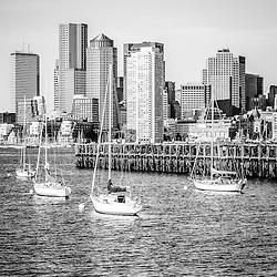 Boston skyline black and white photo with Port of Boston pier, downtown Boston skyscrapers, and sailboats.