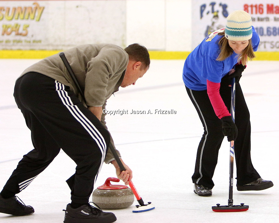 Tony Jacobs, left and Maggie Schaber sweep a stone during a curling match at the Wilmington Ice House. (Jason A. Frizzelle)