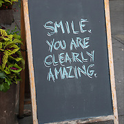 "Humorous sign outside of restaurant, ""Smile, You Are Clearly Amazing""."