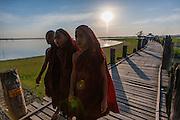 Buddhist monks strolling on U Bein bridge at dusk (Amarapura, Myanmar)