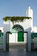 Moroccan Mosque architecture, Asilah, Northern Morocco, 2015-08-03.<br /><br />Asilah is a sleepy fishing town in the North of Morocco, just one hour south of Tangier. While not completely off Morocco's well-beaten path, it's often missed by travellers bound inland for Fez or Chefchaouen, yet has a uniquely alluring charm. With an immaculately restored medina that's re-painted vivid shades of blue & white each summer, Asilah has the feel of being Morocco's own Santorini - a great spot to see the more chilled out, seaside town life in Morocco.  <br /><br />The town lies in the middle of a fascinating history in historical, architectural and artistic terms. It's 3,600 year old history that includes a varied range of occupiers, involving Roman, Arab Portuguese, Spanish and French colonisation. Many famous writers and artists have spent time here; in ancient times is it reported Herecules did a tour of the area and, more recently; Paul Bowles, Tennessee Williams, Edith Wharton, Jean Genet (who is buried in the nearby town of Larache), William Burroughs, Jimi Hendrix and Henri Matisse have all found the area inspiring. The Portuguese ramparts remain fully intact and a full day can be spent wandering through its old gates and the ever narrowing medina streets inside the walls.<br /><br />The architecture in Asilah has been heavily influenced by these different periods of occupation, which is one of the main reasons for its unique and characterful feel. Evidence of Mediterranean design can be seen in the rampart walls and gates themselves, reflecting the Spanish & Portuguese influence on the Asilah's development, Roman ruins can be found in the nearby town of Larache and Arab influences are more subtly found in the decorative window shutters and the labyrinth like medina layout to the streets. <br /><br />If a lover of the quirkier details found in the medinas of Morocco, then Asilah won't disappoint, with hundreds of creatively designed doorways, decorative window shutter