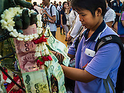 21 NOVEMBER 2015 - BANGKOK, THAILAND: A woman donates 20Baht (about $0.60 US) at the Wat Saket temple fair. Wat Saket is on a man-made hill in the historic section of Bangkok. The temple has golden spire that is 260 feet high which was the highest point in Bangkok for more than 100 years. The temple construction began in the 1800s in the reign of King Rama III and was completed in the reign of King Rama IV. The annual temple fair is held on the 12th lunar month, for nine days around the November full moon. During the fair a red cloth (reminiscent of a monk's robe) is placed around the Golden Mount while the temple grounds hosts Thai traditional theatre, food stalls and traditional shows.     PHOTO BY JACK KURTZ