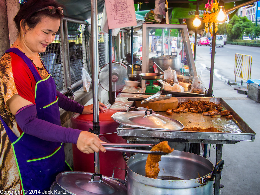 22 AUGUST 2014 - BANGKOK, THAILAND:      A street vendor sells deep fried pork bellies on Sukhumvit Road near Soi 77. The Thai military junta, formally called the National Council for Peace and Order (NCPO), has ordered street vendors off of the sidewalks in an effort to bring order to Bangkok's chaotic sidewalks. Vendors have complained that the new regulations are hurting them economically but largely complied with the military orders.      PHOTO BY JACK KURTZ
