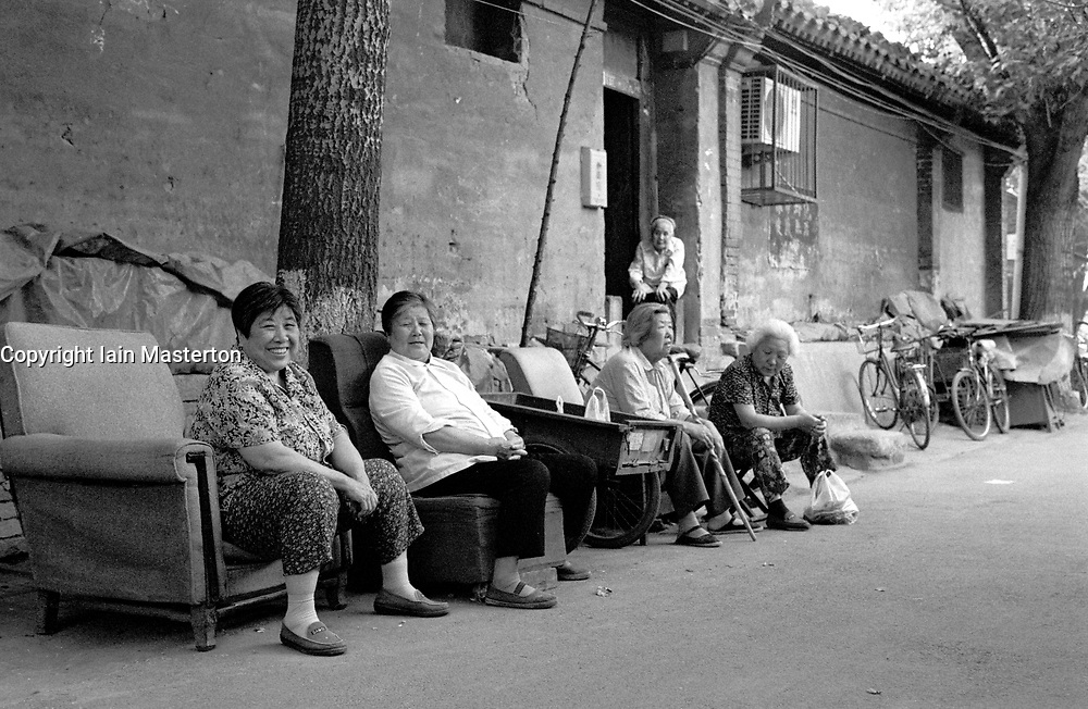Chinese women sitting outside their homes in a Beijing hutong