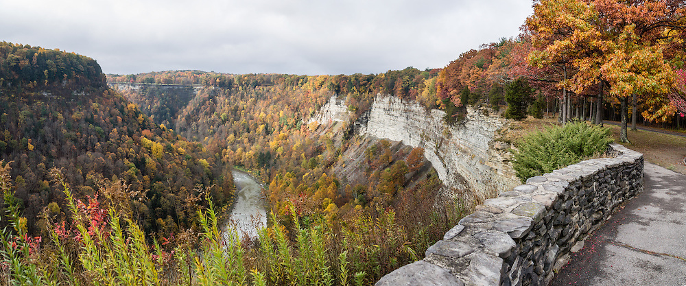 """In Letchworth State Park, renowned as the """"Grand Canyon of the East,"""" the Genesee River roars northeast through a gorge over three major waterfalls between cliffs as high as 550 feet, surrounded by diverse forests which turn bright fall colors in the last three weeks of October. The large park stretches 17 miles between Portageville and Mount Morris in the state of New York, USA. Drive or hike to many scenic viewpoints along the west side of the gorge. The best walk is along Gorge Trail #1 above Portage Canyon from Lower Genesee Falls (70 ft high), to Inspiration Point, to Middle Genesee Falls (tallest, 107 ft), to Upper Genesee Falls (70 ft high). High above Upper Falls is the railroad trestle of Portageville Bridge, built in 1875, to be replaced 2015-2016. Geologic history: in the Devonian Period (360 to 420 million years ago), sediments from the ancestral Appalachian mountains eroded into an ancient inland sea and became the bedrock (mostly shales with some layers of limestone and sandstone plus marine fossils) now exposed in the gorge. Genesee River Gorge is very young, as it was cut after the last continental glacier diverted the river only 10,000 years ago. The native Seneca people were largely forced out after the American Revolutionary War, as they had been allies of the defeated British. Letchworth's huge campground has 270 generously-spaced electric sites. The panorama was stitched from 3 overlapping photos."""