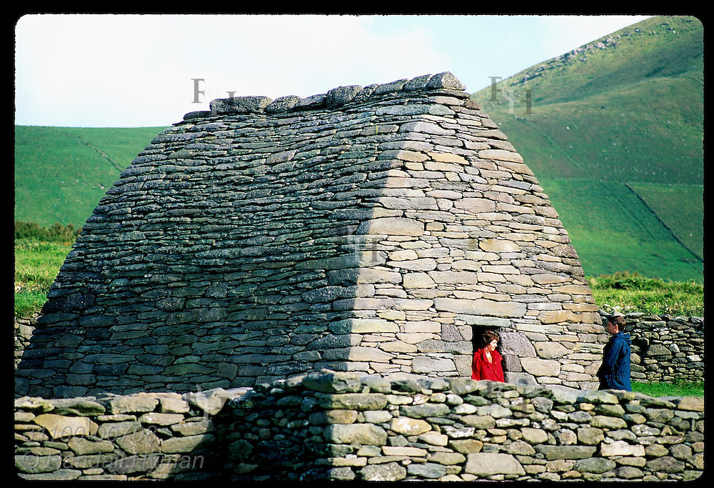 Woman in red jacket exits Gallarus Oratory, best-preserved early Christian drystone church;Dingle Ireland