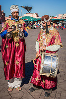 Colourfully dressed street musicians playing  for tourists in Marrakech's Old City.