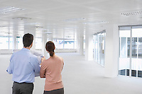 Two office workers looking at plan and empty office space back view