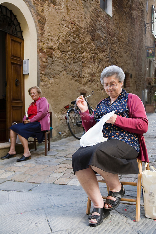 Women sitting on chairs outside houses on main street in late afternoon, Pienza, Tuscany, Italy<br />