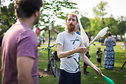 Juggler Nick Aikens, right, gives Benjamin Barlow a juggling instruction during the Makeshift Festival at Tenney Park in Madison, Wisconsin, Sunday, Aug. 12, 2018.