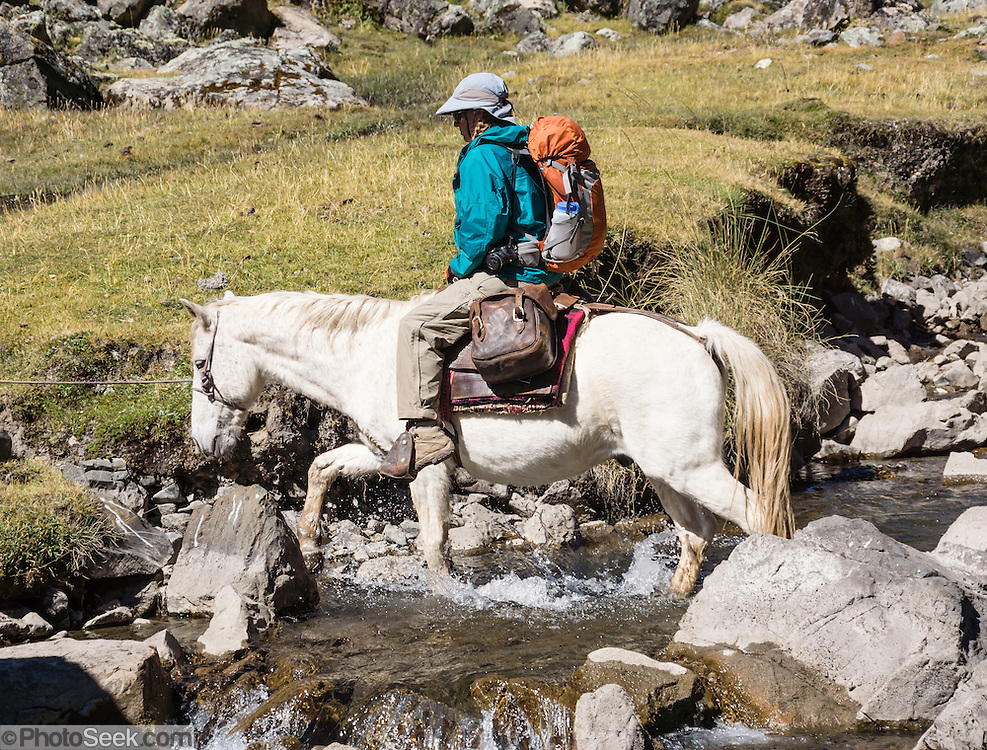 Riding horse across stream in Huanacpatay Valley, Cordillera Huayhuash, Andes, Peru, South America. Day 6 of 9 days trekking around the Cordillera Huayhuash.