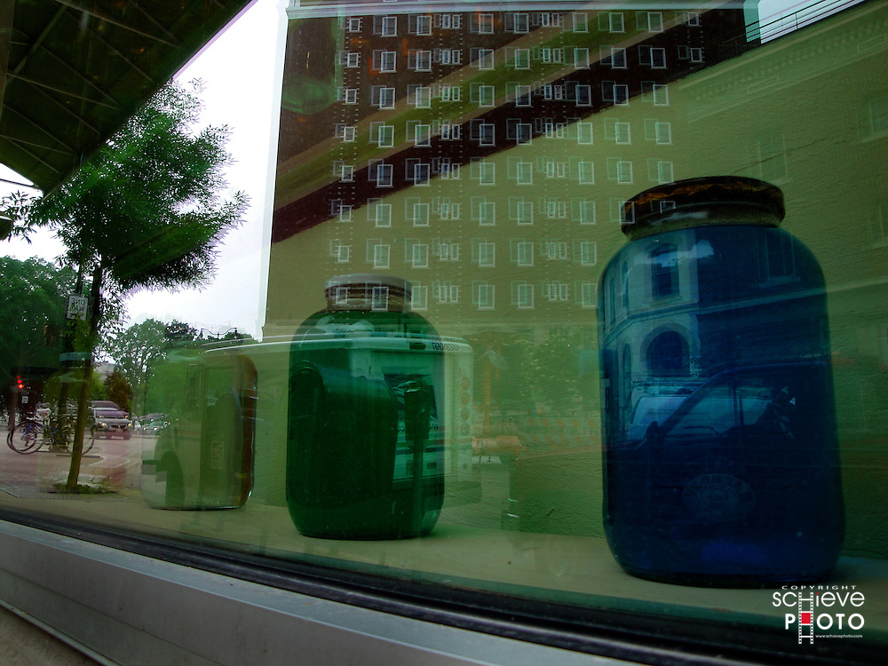 Colored liquid in jars in a window.