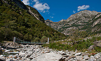 The beautiful Verzasca Valley with a footbridge crossing the rocky expanse of the river in Ticino, Switzerland.