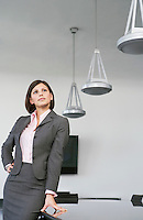 Business woman leaning against table in conference room