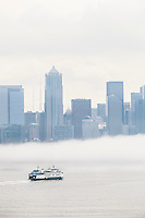 A Washington State Ferry approaching Seattle with a fog bank over downtown Seattle, USA