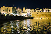MONOPOLI, ITALY - 22 JULY 2018: A night view of the bay by the old city gate in Monopoli, Apulia, Italy, on July 22nd 2018.
