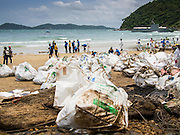 02 AUGUST 2013 - KOH SAMET, RAYONG, THAILAND: Workers fill plastic bags with contaminated absorption pads on Ao Prao beach on Koh Samet island. About 50,000 liters of crude oil poured out of a pipeline in the Gulf of Thailand over the weekend authorities said. The oil made landfall on the white sand beaches of Ao Prao, on Koh Samet, a popular tourist destination in Rayong province about 2.5 hours southeast of Bangkok. Workers from PTT Global, owner of the pipeline, up to 500 Thai military personnel and volunteers are cleaning up the beaches. Tourists staying near the spill, which fouled Ao Prao beach, were evacuated to hotels on the east side of the island, which was not impacted by the spill. Officials have not said when Ao Prao beach would reopen. PTT Global Chemical Pcl is part of state-controlled PTT Pcl, Thailand's biggest energy firm.    PHOTO BY JACK KURTZ