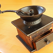 Still-life of an antique hand cranked tabletop coffee grinder. Manufactured by the C.P. Co. the grinder dates back to the late 19th or early 20th century.