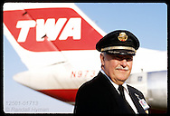 TWA pilot, Captain James Chick, poses with MD-80 tail in back @ Lambert Intl Airport; St. Louis. Missouri
